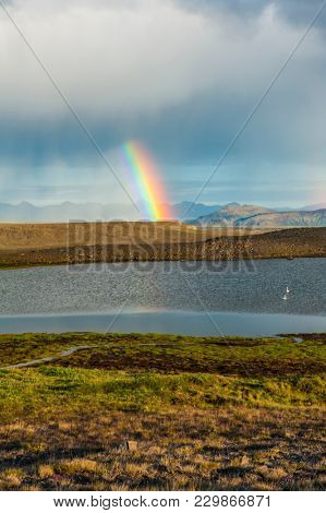 Glacial lake on Iceland and rainy clouds with rainbow