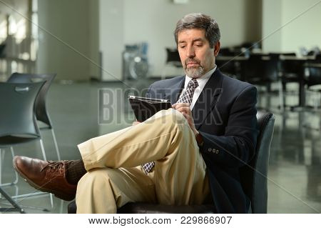 Portrait of Hispanic businessman using electronic tablet inside office building