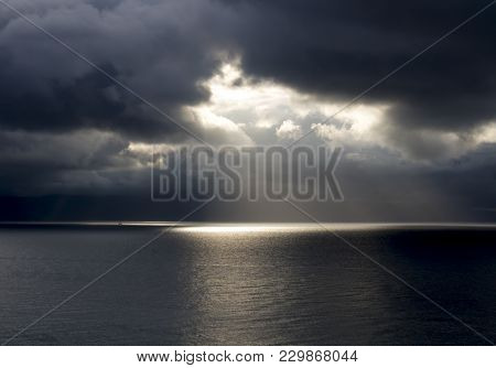 Sun Rays Break Through Heavy Dark Clouds Onto Vast Seascape With One Tiny Boat On Horizon