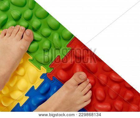 Closeup Of Boy Massaging Feet While Standing On Special Mat