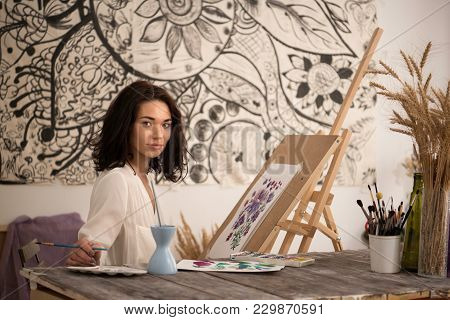 The Portrait Of Happy And  Beatifull Female Artist Drawing The Picture At Her Studio.looking At Came