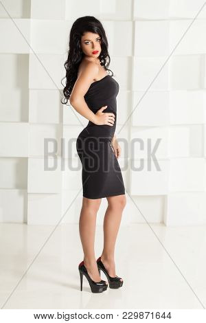 Fashion Portrait Of Beautiful Brunette Woman Wearing Black Cocktail Dress And High Heels Shoes On Wh
