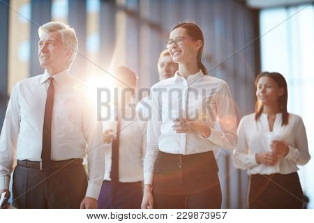 Young businesswoman with drink, her mature colleague and three more associates looking straight