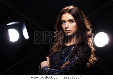 Portrait Of Beautiful Female Model In Blue Evening Dress Posing At Photo Studio In Light Flashes