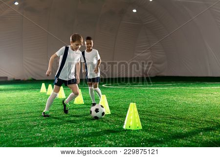 Two little football players running after ball while exercising on pitch with cones
