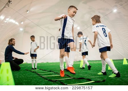Team of several sporty boys training on green pitch before game or football competition