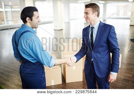Young businessman in suit and delivery man in uniform handshaking after relocation work