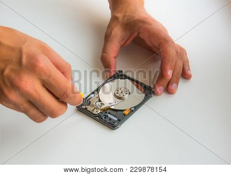 Two Man Hands Fixing Damaged Hard Disc Using Screwdriver. Close-up