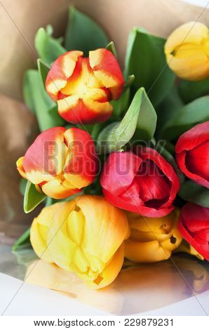 Bouquet Of Red And Yellow Spring Tulips Wrapped In Brown Paper