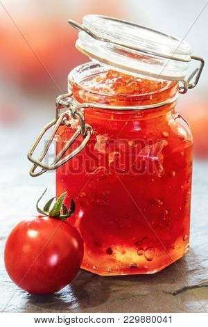 Tomato Jam in a glass jar on a slate table top