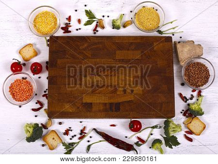 Food Frame Around Empty Brown Cutting Board On White Wooden Table. Organic Food For Healthy Nutritio