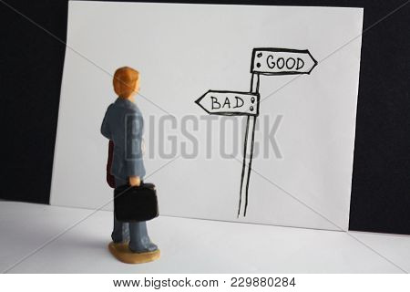 Good versus bad way. Miniature man looks on handdrawn guidepost and decides about future. Good, evil, business fair access topic. poster
