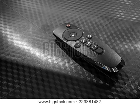 Universal Remote Control Isolated On Black Texture Background. Modern Tv Remote Controller.