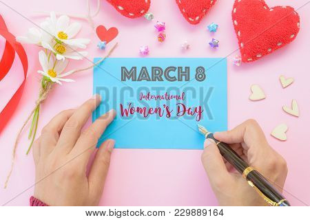 Woman Hand Holding Black Pen And Writing Happy International Women's Day Message On Blue Paper With