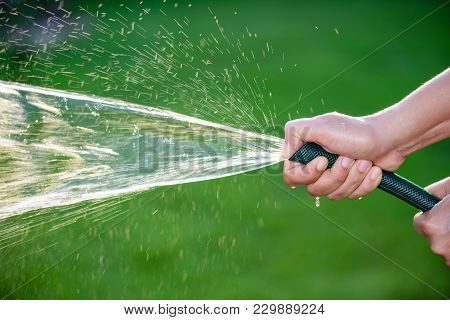 Woman Hand Holding Rubber Water Hose And Using Finger Close End Of Rubber Water Hose To Make  Water