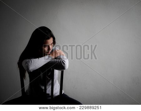 Depressed Broken Hearted Woman Sitting Alone On A Wooden Chair In Dark Room At Home. Lonly , Sad, Lo