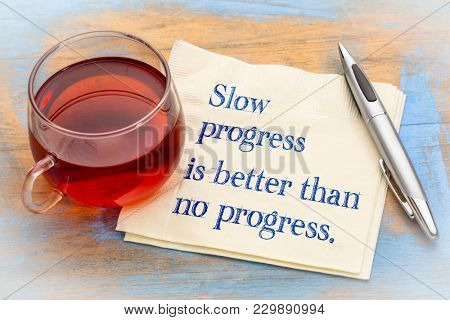 Slow progress is better than no progress inspirational note - handwriting on a napkin with a cup of coffee