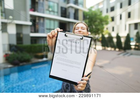 Female Hand Holds Out Pen And Contract To Sign. Sunny Portrait On Building Background With New Apart