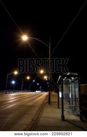 City bridge road with bus stop at night