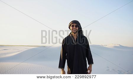 Attractive Young Sheikh With Smile On Face Looks Into Camera And Goes Forward, Stops And Takes Off G