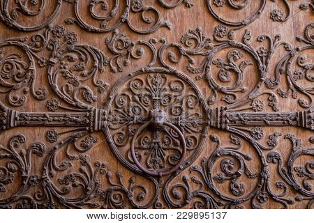 Old wooden door with a metallic pattern close-up. The cathedral Notre-Dame de Paris