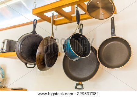 Saucepan And Other Kitchenware Hanging On The Wall