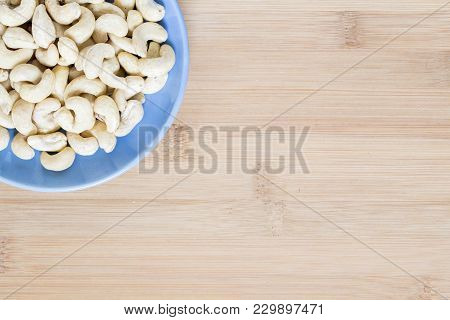 Cashew In Blue Plate On Wooden Background. Raw Cashew Nut For Food. Organic Food Banner Template Wit
