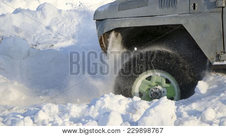 The Wheel Of The Car Is Stuck In The Snow. Spray Of Snow From The Rotating Wheel Of Winter Tires. Sl