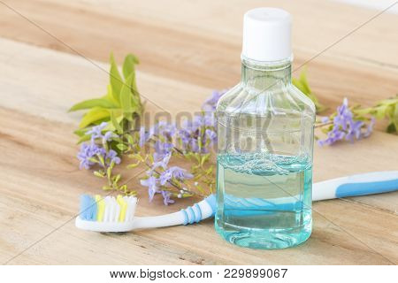 Mouthwash And Toothbrush For Healthy Care Oral Cavity On Background Wooden