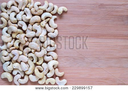 Cashew Pile On Wooden Background. Cashew Photo Wallpaper. Organic Food Rustic Banner Template With T