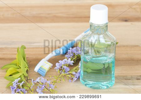 Mouthwash And Toothbrush For Health Care Oral Cavity On Background Wooden