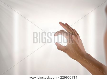 Digital composite of Hand interacting and pinching with bright light shining through fingers