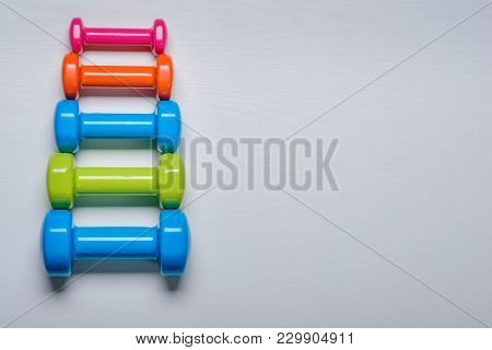 Many Blue Green And One Orange In The Middle Dumbbells On A White Background ,concept Preparing To F