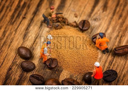 Miniature Figures Working On Instant Coffee Macro Photography On Wood Table