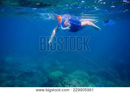 Woman Learns To Snorkel In Full Face Mask. Underwater Coral Landscape And Snorkel. Female Swimmer In