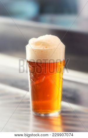 Fresh Served Pint Of Frothy Draft Beer In A Glass