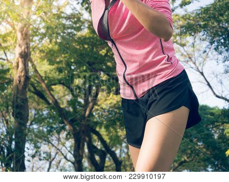 Asian Young Woman On Mark To Set Ready For Jogging Exercise To Buld Up Her Body On Glass In Warm Lig