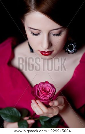Young Surprised Woman In Red Victorian Epoch Clothes With Red Rose On Dark Background