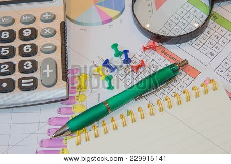 Sales Report Analysis With Pen And Calculator. Business Accessories ( Magnifier, Calculator, Fountai