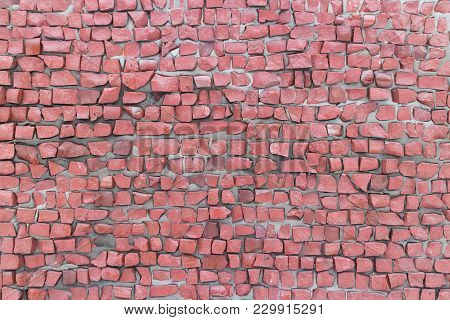 Pink Smalt Pebbles On Gray Cement Wall.