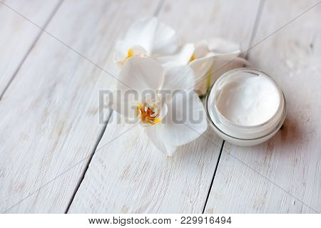 Pot Of Moisturizing Face Cream And Beautiful White Orchid Flowers