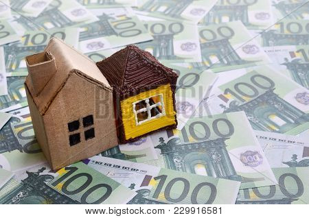 Small Toy House Is Lies On A Set Of Green Monetary Denominations Of 100 Euros. A Lot Of Money Forms