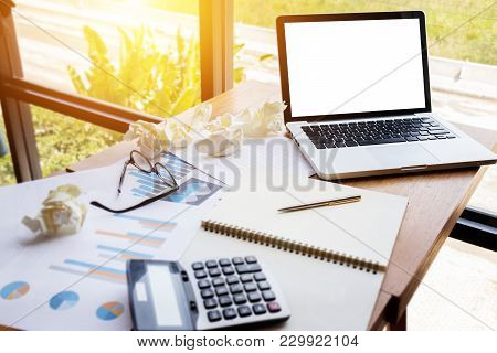 Chart And Graph Account With Calculator On Table Work Space With Blank Screen Computer Laptop .busin