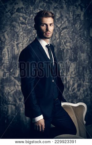 Portrait of a handsome man in an elegant suit on a grunge background. Studio shot.