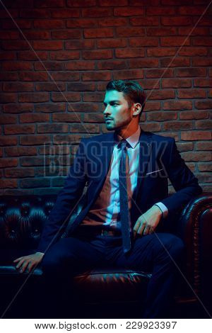 Respectable handsome man in elegant suit sitting in apartments with classical luxurious interior. Men's beauty, fashion.