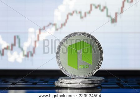 Neo Cryptocurrency; Physical Concept Neo Coin On The Background Of The Chart