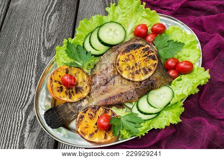 Flounder Cooked On Brazier With Oranges. Served On Metal Plate With Lettuce, Fried Oranges, Cucumber