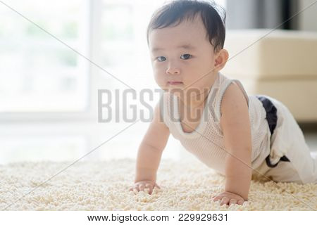 Chinese baby boy crawling on floor. Asian family at home, living lifestyle indoors.