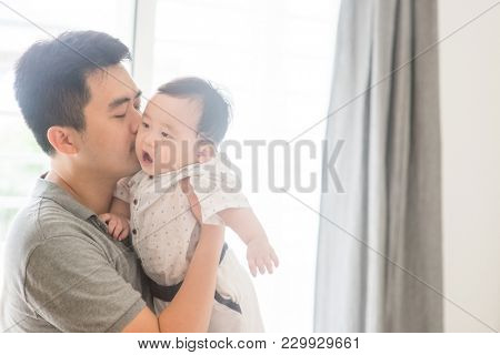 Happy Asian family at home. Father kissing child, living lifestyle indoors.