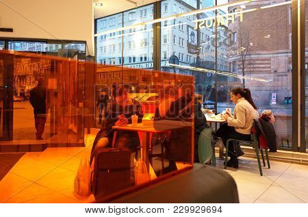 Sweden, Stockholm - February 10, 2018: Girls using smartphones behind orange wall in Max hamburger restaurant in city center of Stockholm